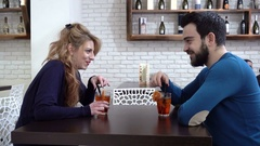 First date: Man and woman flirting with a cocktail in a bar Stock Footage