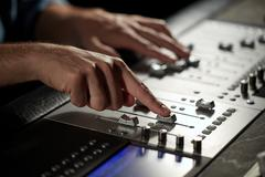 Hands on mixing console in music recording studio Stock Photos