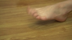 Young girl shakes her feet and fingers on one leg at home Stock Footage