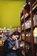 Beautiful woman smelling a jar of spice Stock Photos