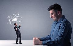 Young businessman fighting with miniature businessman Stock Photos