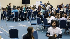 Young people crowd sit at tables in hall during innovation science exhibition Stock Footage