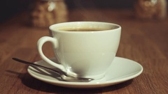 Woman hand with black nail polish take steaming cup of coffee of wooden table Stock Footage