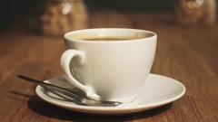 White cup of steaming hot coffee drink on saucer upon wooden table Stock Footage