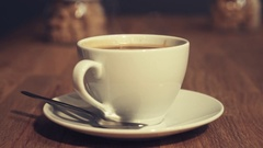 White cup of steaming hot coffee drink on saucer upon wooden desk Stock Footage