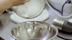 Woman hand pours cream from one pan into another Stock Footage