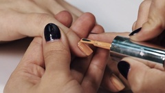 Woman cosmetician hand apply beige polish on nails in manicure salon white table Stock Footage