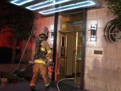 2 firefighters enter building, hose dangles, flashing lights, siren bg Stock Footage