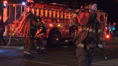 Night, 4 Firefighters carry hose bundles into apartment building, DC Stock Footage