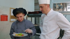 Young male trainee enjoying shrimp salad made by chef Stock Footage