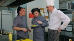 Young cook trainees tasting seafood dish made by chef Stock Footage