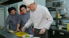 Chef learning his trainees how to decorate shrimp salad on a white plate Stock Footage
