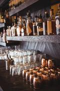 Bottles and glasses arranged on shelf in a bar Stock Photos