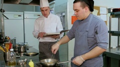 Chef with cookbook instructing cook trainee how to fry shrimps Stock Footage
