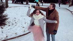 Modern beautiful couple having fun skating on the outdoor rink in winter Stock Footage