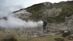 Young man tourists on thermal field watching at natural volcanic hot springs Stock Footage