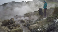 Young women standing on thermal field in clouds of steam hot springs Stock Footage