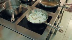 Dishes in frying pans being cooked on a stove while chef regulating temperature Stock Footage