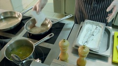 Chef putting floured fish in frying pans while another cook mashing potatoes Stock Footage