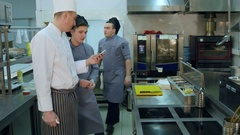 Senior chef showing something on his phone to young male cook trainee Stock Footage
