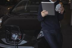Man using digital tablet while charging electric car Kuvituskuvat
