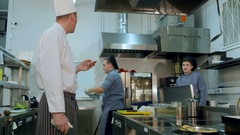 Head chef reading online orders from his phone and giving tasks to cooks Stock Footage