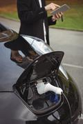 Car being charged with electric car charger Stock Photos