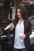 Woman using mobile phone while car being charged in background Stock Photos