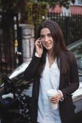 Woman talking on mobile phone while car being charged in background Stock Photos