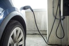Close-up of car being charged with electric car charger Stock Photos