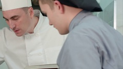 Young male trainees watching head chef cooking from the cookbook Stock Footage