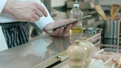 Chef holding tablet computer while cook using sunflower oil Stock Footage