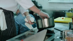 Experienced chef's male hands cooking meal on a stove Stock Footage