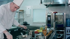 Busy chef cooking mashed potatoes with a whisker in the professional kitchen Stock Footage