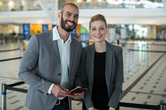 Portrait of smiling businesspeople with passport waiting in queue Stock Photos