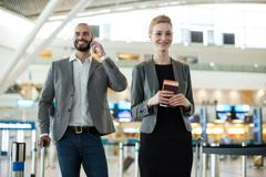Businesspeople waiting in queue at a check-in counter with luggage Stock Photos