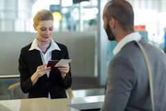 Commuter standing at counter while attendant checking his passport Stock Photos