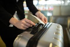 Airline check-in attendant sticking tag to the luggage of commuter Stock Photos