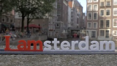 View of small plastic figure of Iamsterdam letters sculpture on the bridge Stock Footage