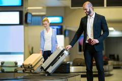 Businessman picking his luggage from baggage claim area Stock Photos