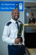 Smiling airport security officer holding metal detector in airport terminal Kuvituskuvat