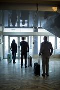 Business people with luggage standing at waiting area in airport Stock Photos