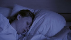 Restless dreams of sleeping woman interrupted by waking up for nightmares Stock Footage