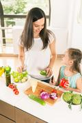 Cute little girl cooking with her mother, healthy food Stock Photos