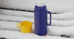 A thermos of hot coffee on a snowy bench Stock Footage
