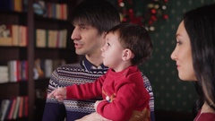 Young family sometimes look to the side and talk in the living room of his cozy Stock Footage