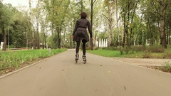 Inline skates. Stylish woman moving on roller skates. The view from the back. 4K Stock Footage