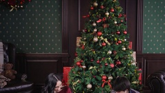 Well-dressed happy family sitting on the rug near the Christmas tree in a warm Stock Footage