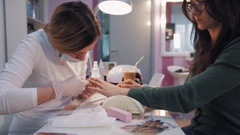 Woman in glasses get manicure by blonde in surgical gloves in beauty saloon Stock Footage