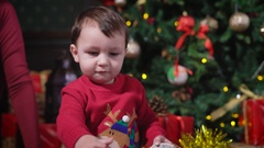 Little boy with dark hair, wearing a red sweater, deer playing with yellow shiny Stock Footage